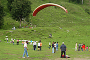 India, Vashisht near Manali, Kullu District, Himachal Pradesh, Northern India local tourists enjoying a day of sport and recreation on the mountain side with gliders