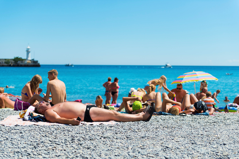 People enjoy a summer day on the beach in the Crimean port of Yalta, in southern Ukraine. The man in the foreground is wearing Adidas swimming briefs and clutching his mobile phone.