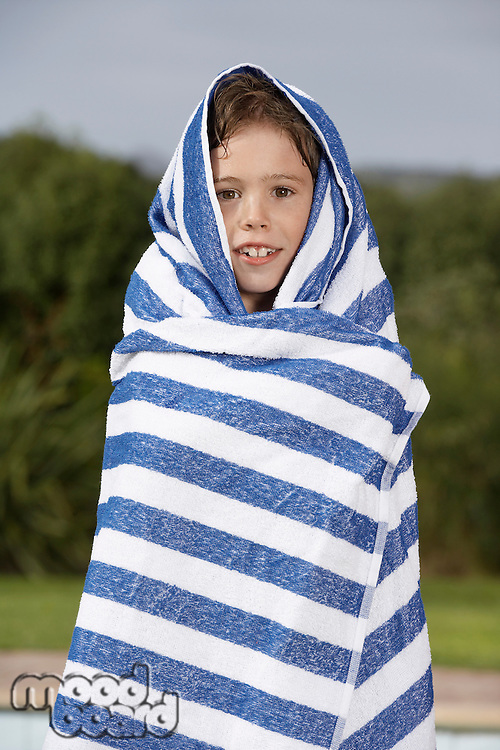 Portrait of boy (5-6) wrapped in striped towel