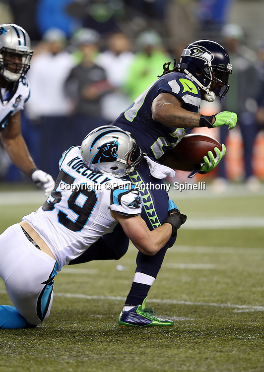 Seattle Seahawks running back Marshawn Lynch (24) gets tackled by Carolina Panthers middle linebacker Luke Kuechly (59) as he runs for a gain of second quarter gain of 8 yards during the NFL week 19 NFC Divisional Playoff football game against the Carolina Panthers on Saturday, Jan. 10, 2015 in Seattle. The Seahawks won the game 31-17. ©Paul Anthony Spinelli