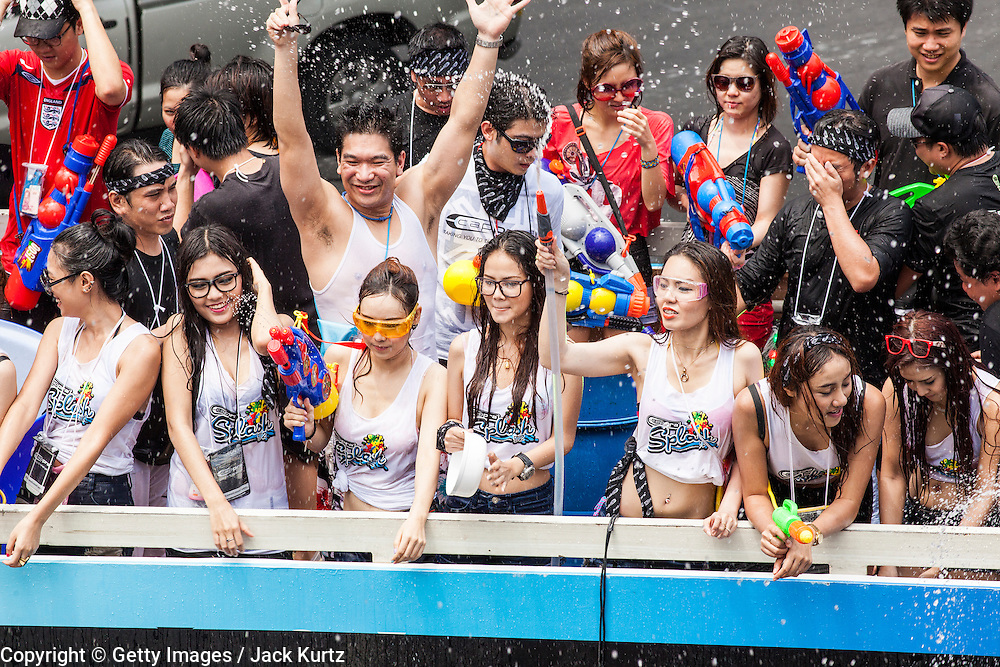 14 APRIL 2013 - BANGKOK, THAILAND:  Women on a chartered bus participate in a community water fight on April 14, 2013 in Bangkok, Thailand. The Songkran festival is celebrated in Thailand as the traditional New Year's Day from 13 to 15 April. The throwing of water originated as a way to pay respect to people and is meant as a symbol of washing all of the bad away. PHOTO BY JACK KURTZ