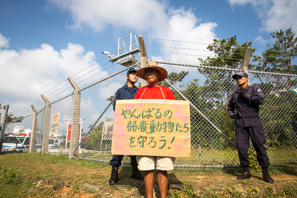 OKINAWA, JAPAN - AUGUST 19 : Anti U.S base protester with protest sign protest against the construction of helipads in front of the main gate of U.S. military's Northern Training Area in the village of Higashi, Okinawa Prefecture, on August 19, 2016. Japanese government resume construction of total six helipads in a fragile ten million year old Yanbaru forest that is home to endemic endangered species such as the Okinawan rail and Okinawa wood pecker. (Photo by Richard Atrero de Guzman/NURPhoto)