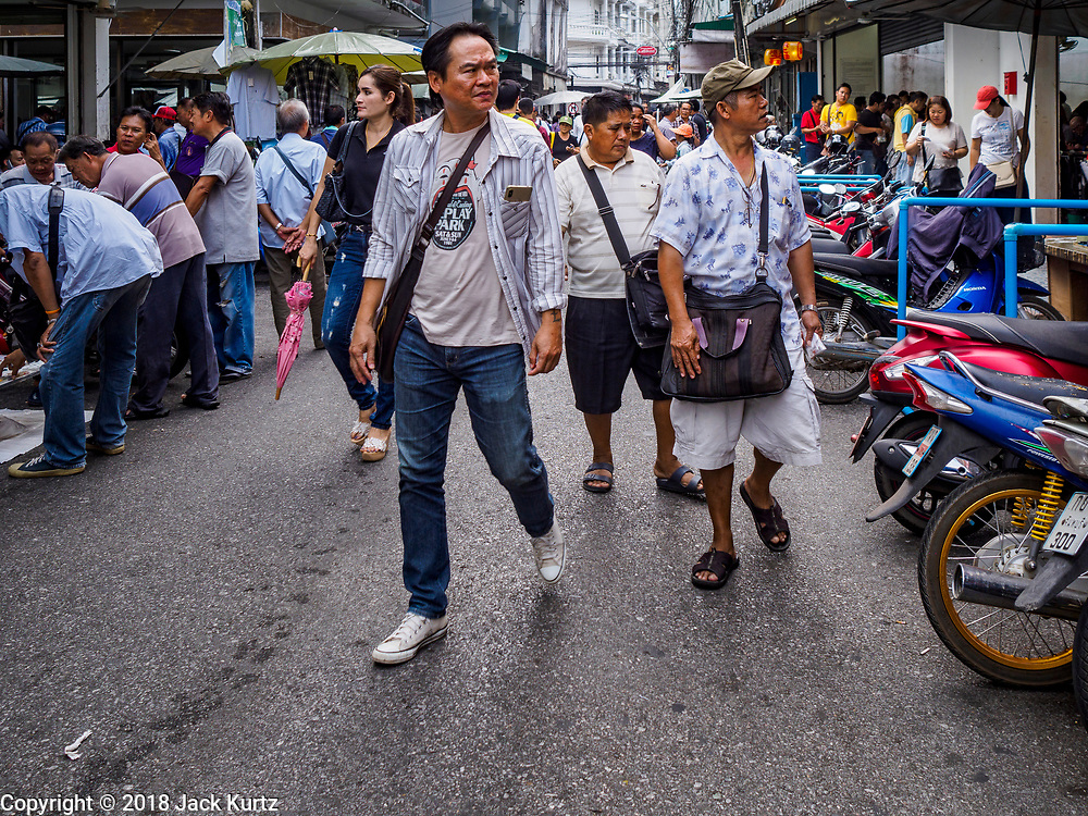22 DECEMBER 2018 - CHANTABURI, THAILAND: Men walk through the gem market in Chantaburi. The gem market in Chantaburi, a provincial town in eastern Thailand, is open on weekends. Chantaburi used to be an active gem mining area in Thailand, but the mines are played out now. Now buyers and sellers come from around the world to Chantaburi for the weekend market. Many of the stones come from Myanmar, others come from mines in Afghanistan and Africa.      PHOTO BY JACK KURTZ