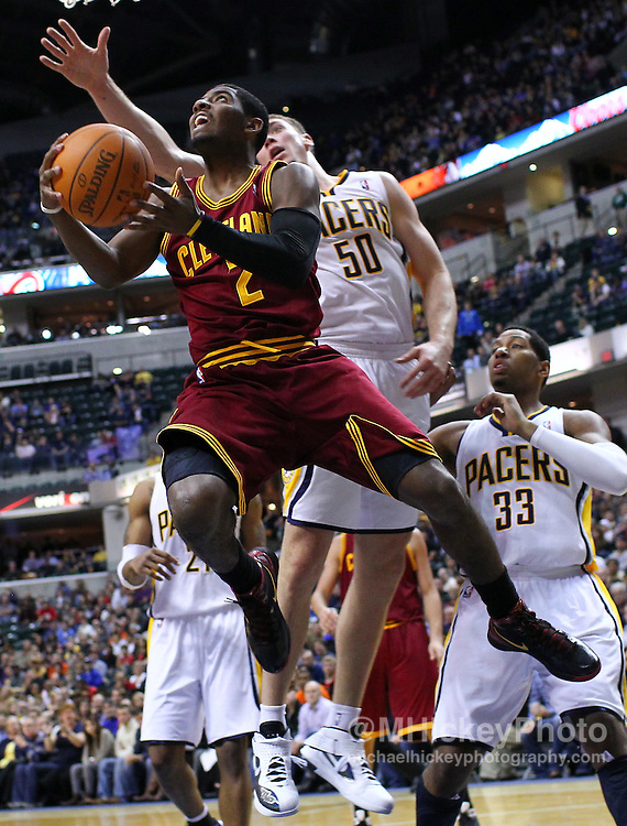 Dec. 30, 2011; Indianapolis, IN, USA; Cleveland Cavaliers guard Kyrie Irving (2) puts the ball up as Indiana Pacers power forward Tyler Hansbrough (50) defends from behind at Bankers Life Fieldshouse. Indiana defeated Cleveland 81-91. Mandatory credit: Michael Hickey-US PRESSWIRE