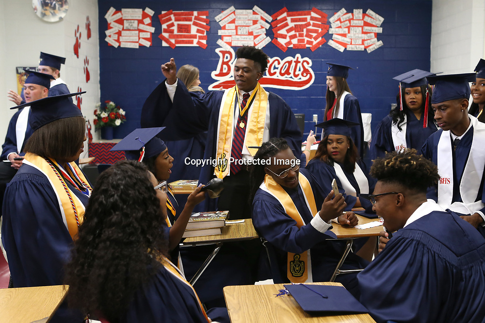 Baldwyn High School seniors, including Jalon Clark, center, sit in a classroom as they wait for the start of their graduation ceremony at the school Friday night.