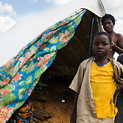 A woman and her children stand in front of the tent where they now live after their home was destroyed by floods in the village of Kpoto, Benin on Tuesday October 26, 2010. Waters have receded in Kpoto, but most of the village was literally flattened by floods that have hit Benin over the past few weeks. Almost all of the village's 1500 people have moved to a location near the local church, located about 500 meters away, where they now live in basic shelters.