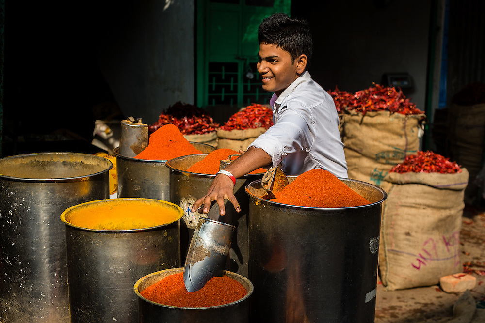 A boy attends to his spices in a spice stall, in Udaipur's street market.