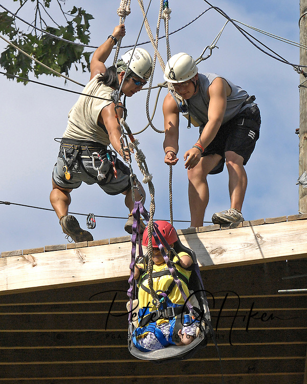 Directv Magazine -- Minda Cox gets guided down the zip line by Camp Barnabas counselors.