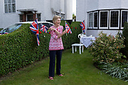 As the Coronavirus lockdown continues over the May Bank Holiday, the nation commemorates the 75th anniversary of VE Day (Victory in Europe Day, the day that Germany officially surrendered in 1945) and in Dulwich, neighbours and residents emerge from their homes to party while still observing social distancing rules. A local lady resident jokes about learning semiphore with Union Jack flags in the front garden of a neighbour, on 8th May 2020, in London, England.