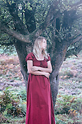 a blonde woman with a red dress is standing under a tree