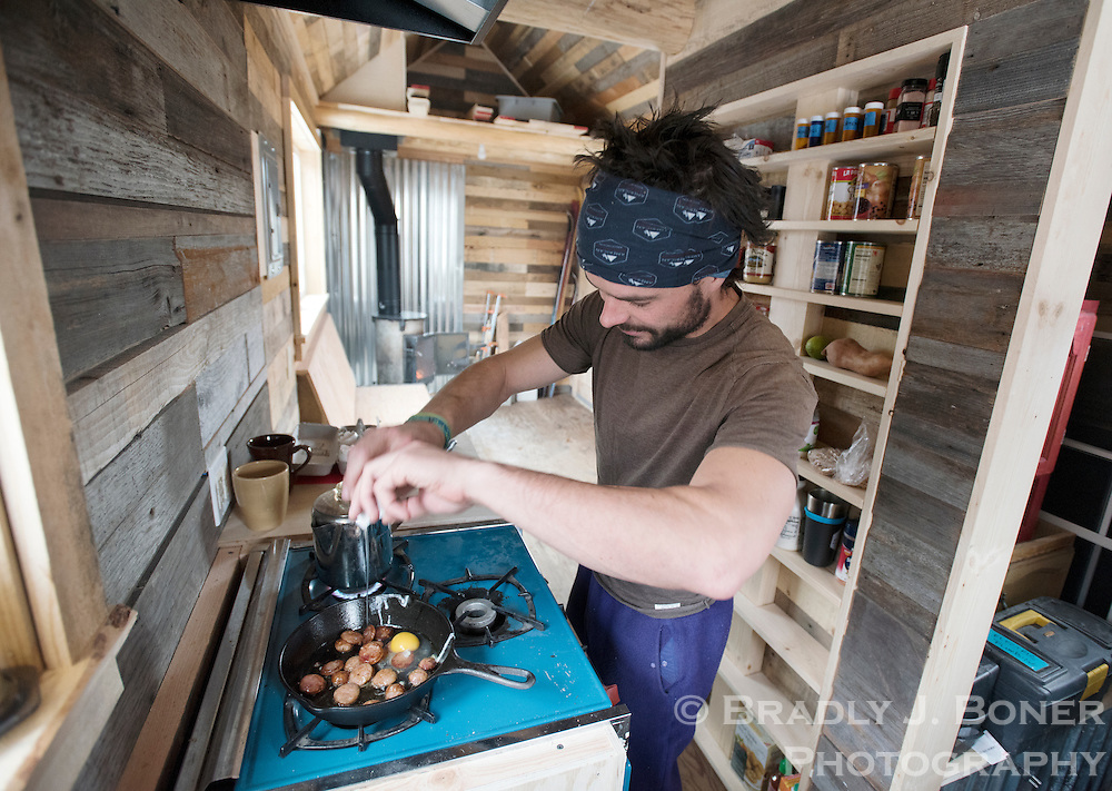 Adam Glos cooks breakfast on a small stove he found at a Habitat ReStore in Idaho Falls. As of mid-November, Glos had only the bathroom and flooring to finish in his tiny house project.