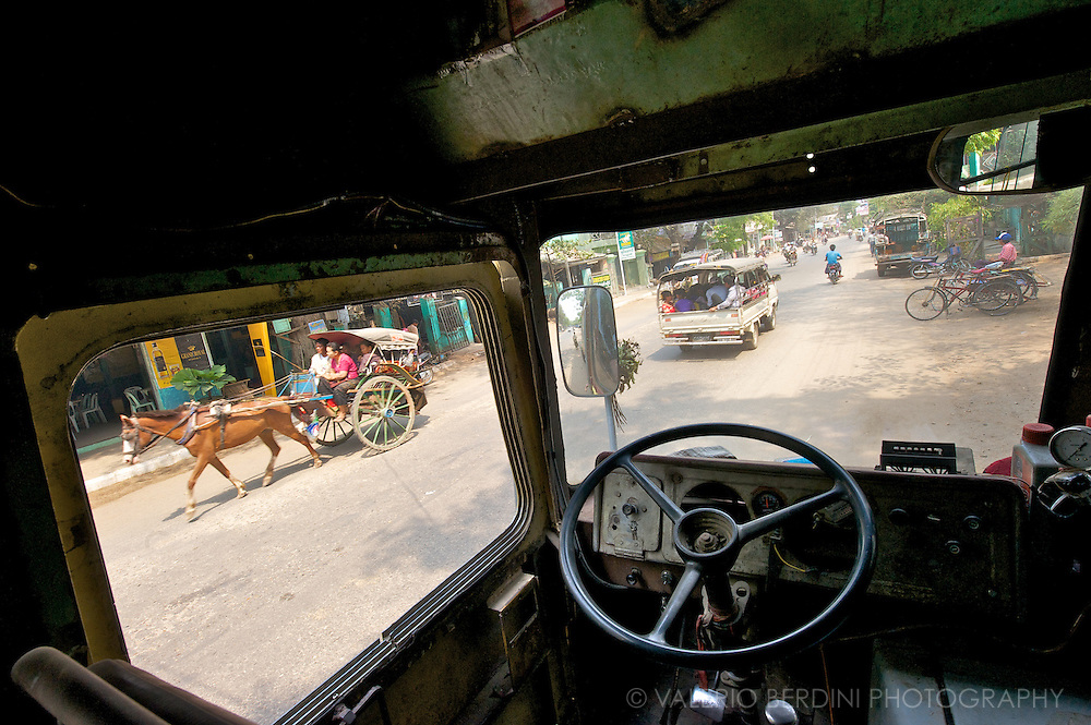 A view of a village street through the windows of an old bus. Some of the several means of transport used in Burma are visible.