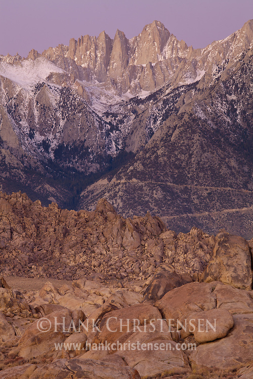 Dawn begins to light Mt. Whitney and the wild rock formations of the Alabama Hills