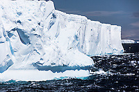 Huge tabular Icebergs slowly ride the Southern Ocean currents, migrating along the Antarctic Peninsula to disappear in the world's oceans.  Antarctica, The Antarctic continent.