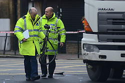 © Licensed to London News Pictures.18/11/2013. London, UK. Police officers investigating the scene where a male cyclist believed to be aged in his early 60s was killed by a truck in Camberwell Road, junction with Albany Road, SE5, London.Photo credit : Peter Kollanyi/LNP