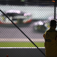 A crew member watches the race action from behind a fence during the NASCAR Sprint Unlimited Race at Daytona International Speedway on Saturday, February 15,  2014 in Daytona Beach, Florida.  (AP Photo/Alex Menendez)