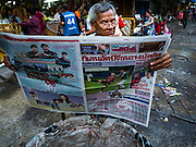 30 JUNE 2016 - BANGKOK, THAILAND: A porter reads a Bangkok newspaper while he waits for customers in front of Pak Khlong Talat. Sidewalk vendors around Pak Khlong Talat, Bangkok's famous flower market, face eviction if they reopen on July 1. As a part of the military government sponsored initiative to clean up Bangkok, city officials have been trying to shut down the sidewalk vendors around the flower market. The vendors were supposed to be gone by the end of March, but city officials relented at the last minute with a compromise allowing vendors to stay until June 30. When vendors dismantled their booths after business on June 30, they weren't sure if they will be allowed to reopen July 1. Some vendors have moved to new locations approved by the government but many have not because they can't afford the higher rents in the new locations.      PHOTO BY JACK KURTZ