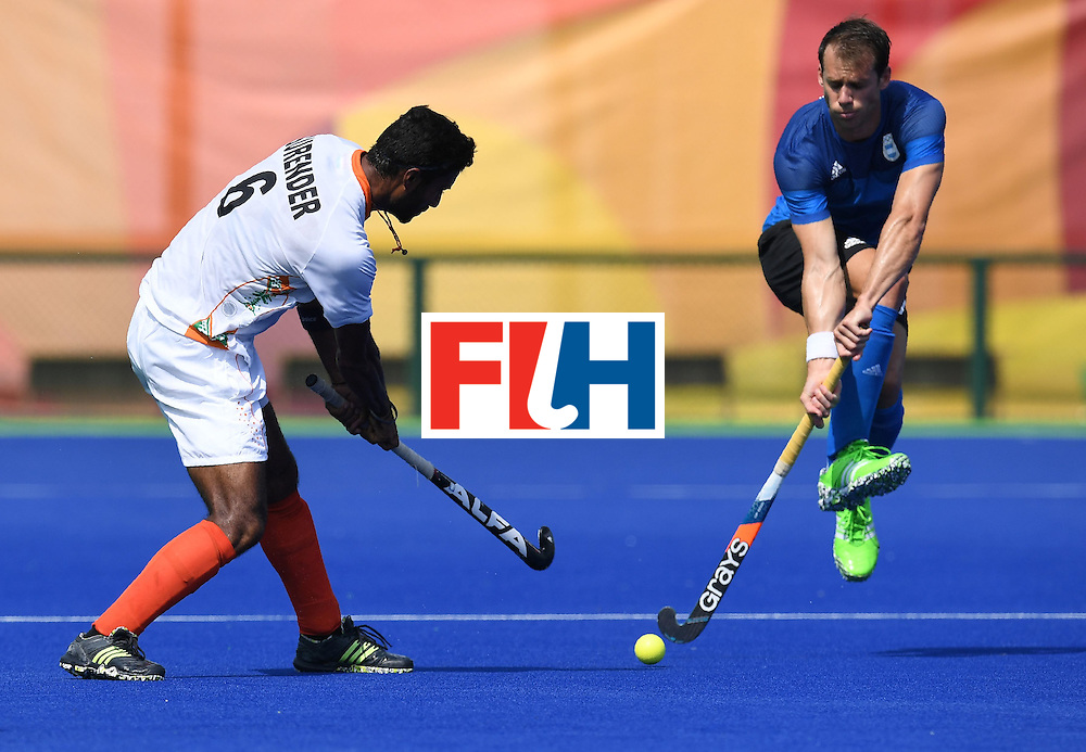 India's Surender Kumar (L) hits the ball past Argentina's Facundo Callioni during the men's field hockey Argentina vs India match of the Rio 2016 Olympics Games at the Olympic Hockey Centre in Rio de Janeiro on August, 9 2016. / AFP / MANAN VATSYAYANA        (Photo credit should read MANAN VATSYAYANA/AFP/Getty Images)
