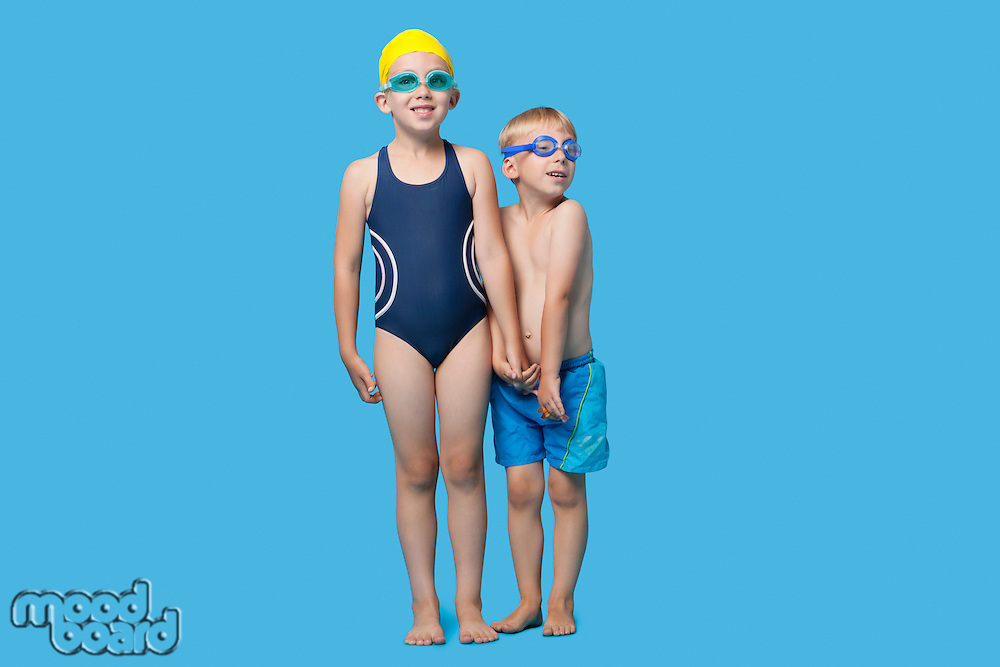 Happy young boy and girl in swimwear holding hands over blue background