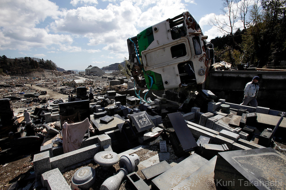 A walks passed a train which was washed ashore on the cemetery in Onagawa, Miyagi, Japan after on March 27, 2011 after massive earthquake and tsunami hit northern Japan. More than 20,000 were killed by the disaster on March 11.<br /> Photo by Kuni Takahashi
