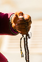 A Tibetan pilgrim fingers her prayer beads, Tandruk Monastery, near Tsedang, Tibet (Xizang), China.