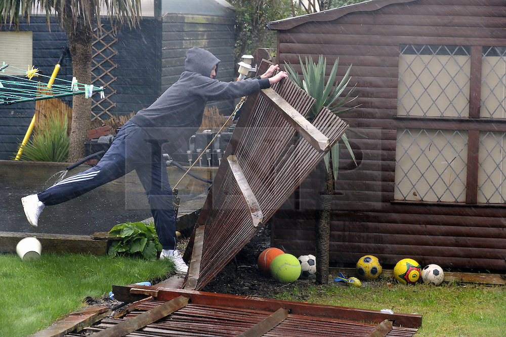© Licensed to London News Pictures. 03/01/2012. London, UK. A man attempts to stop his fence from blowing over in St Pauls Cray, London on January 3rd, 2012.The Met Office has issued a severe weather warning as heavy rain and 85mph winds battered Britain. Photo credit : Grant Falvey/LNP