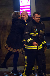 © licensed to London News Pictures. London, UK 27/02/2014. A woman giving a kiss to a fireman after being carried across the street by fire brigade where a burst main has flooded Clapham Road in south London on Thursday, 27 February 2014. Photo credit: Tolga Akmen/LNP