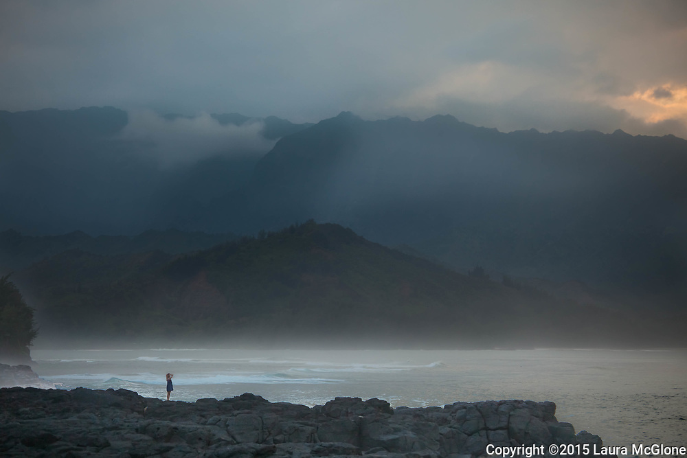Girl standing in awe by ocean & mountains, Kauai Hawaii