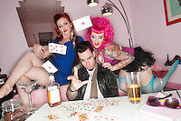 Portrait of man throwing cards in air with two sexy women sitting besides him