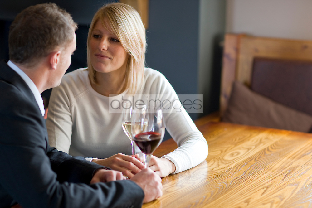 Couple sitting at a table drinking wine