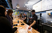 Working Draft Beer Company owner Ryan Browne takes orders inside the taproom in Madison, Wisconsin, Thursday, March 22, 2018.