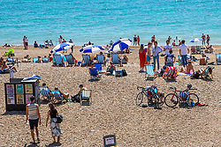 © Licensed to London News Pictures. 30/05/2020. Brighton, UK. Groups of more than 6 people can be seen on the beach in Brighton and Hove as members of the public take to the seaside on the hottest day of the year so far.  Photo credit: Hugo Michiels/LNP