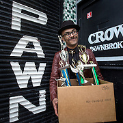 "WASHINGTON,DC - MAR19: Justin Cannon, the founder of The Quitters Club, holds a box of trophies he bought once to use in an art project, outside a pawn shop on 14th Street in Washington, DC, March 19, 2015. He also feels the trophies symbolize people's unnecessary need to succeed in everything. He's quit efforts at film making, graphic design, fashion, and music. The tagline of the Quitters Club is, ""Let's give up on our dreams together."" (Photo by Evelyn Hockstein/For The Washington Post)"