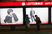 Lotte Department Store. Tourists from Japan have their pictures taken with ad posters featuring Korean soap opera actor Bae Yong-Jun, who is popular in Japan as well.