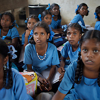 Anjalakshi Krishnamurthy (age 10, wearing beads) with fellow-pupils in class at the Government Girls High School, Venugopalapuram in Cuddalore. ..The five Krishnamurthy sisters from Pudupettai were placed in the Government Home for Tsunami Children in Cuddalore, Tamil Nadu when they lost their mother to the 2004 tsunami. Their father, Krishnamurthy, had decided he could no longer provide day-to-day care for his daughters. Krishnamurthy later remarried. The Krishnamurthy sisters now range in age from eight to sixteen...The four younger sisters are still at the Governement home (or orphanage). In summer 2009, Sivaranjini, the eldest aged sixteen, failed her 10th Standard exams and had to drop out of school so leaving her not eligible for care at the Government home. She is now living with her father and his new wife Nagamalli's house 30km away in Pudupettai. Krishnamurthy is intending that Sivaranjini marry a second cousin in 2010. ..Krishnamurthy visits the Government orphanage once a week to see his four younger daughters. Nagamalli is popular with all five sisters. She provides them attention when they are together and is genuinely interested in their well-being. Sivapriya remains close to her paternal aunt Kamasala with whom she used to live in the fishing village of Thazanguda. Kamasala visits Sivapriya at the orphanage every fortnight. The sisters return to their father's home for festivals including Diwali and the Pudupettai village temple festival...According to Revathi, the staff member in charge at the Government home, the absence of the elder Sivaranjini has had the effect of making the remaining four sisters still at the home increasingly independent. For instance, where they used to all sleep together the girls now sleep in different dormitories. The eldest of these four, fourteen year-old Sivapriya has adopted some of the responsibilities of her elder sisters including coordinating clothes washing and helping her younger siblings with school work. Accord