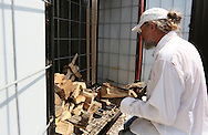 Charles Finch removes firewood from a storage box outside Verona and loads it into his pickup truck in Cedar Falls, Iowa on Tuesday, July 10, 2012. Finch sold firewood to the restaurant which used it for cooking.