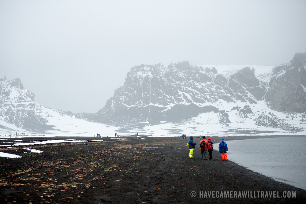 The beach of Whalers Bay on Deception Island with snow falling. Deception Island, in the South Shetland Islands, is a caldera of a volcano and is comprised of volcanic rock.