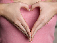 Woman making heart shape with hands close-up mid section