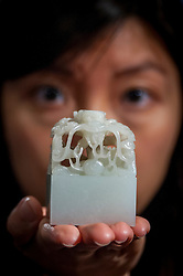 "© Licensed to London News Pictures. 03/11/2016. London, UK. An Imperial pale celadon jade Qing dynasty ""Ziqiang Buxi"" seal, est. GBP500-700k is shown at the preview of Chinese artworks entitled ""Treasures Of The Song & Qing Dynasties"" to be auctioned at Sotheby's in November.  Made of white jade, the seal has a knob in the shape of coiled dragons.  Photo credit : Stephen Chung/LNP"