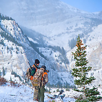 two rifle hunters on ridge talking with huge mountain background