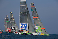 America's Cup yachts surge over start line as timing boat's clock flashes from zero and counts backwards,  signalling start of fleet race; Valencia, Spain.