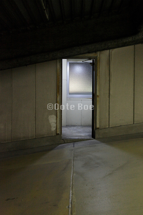 pedestrian door in a parking garage with light coming from the hall