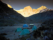 Morning alpenglow on the four summits of Huandoy brings no warmth to the tents still locked in the icy morning freeze at Pisco Base Camp 4,700m.