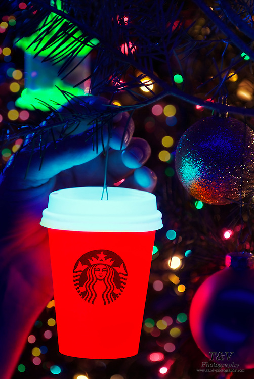 A glowing Starbucks coffee cup is hung on a Christmas tree next to other ornaments.Black light