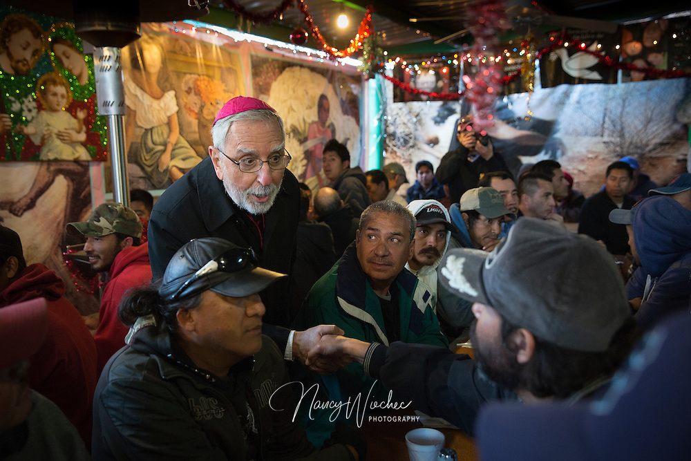 "Bishop Gerald F. Kicanas of Tucson greets men at the ""comedor,"" the kitchen and dining hall of the Aid Center for Deported Migrants in Nogales, Mexico, Dec. 20.  Bishop Kicanas and Nogales Bishop Jose Leopoldo Gonzalez Gonzalez visited with migrants after taking part in a bi-national ""posada,"" a commemoration of Mary and Joseph's search for a place to give birth to Jesus. (CNS photo/Nancy Wiechec)"