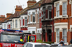 © Licensed to London News Pictures. 16/04/2020. London, UK. A house on Alric Avenue with a fire damaged facade with a fire engine parked in the foreground. The Metropolitan Police Service were called at 02:15BST to a residential address in Alric Avenue NW10 following reports of a fire. Police officers attended with the London Fire Brigade (LFB) and London Ambulance Service (LAS). A 36-year-old woman was taken to hospital with serious injuries. She was pronounced dead at 06:07BST. Another woman, aged in her 60s, was also taken to hospital and treated for non life-threatening injuries. A man in his 40s was arrested on suspicion of arson and taken into police custody. Photo credit: Peter Manning/LNP