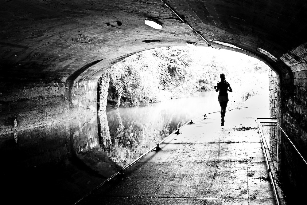 Dramatic black and white image of a female jogger running thru a tunnel.