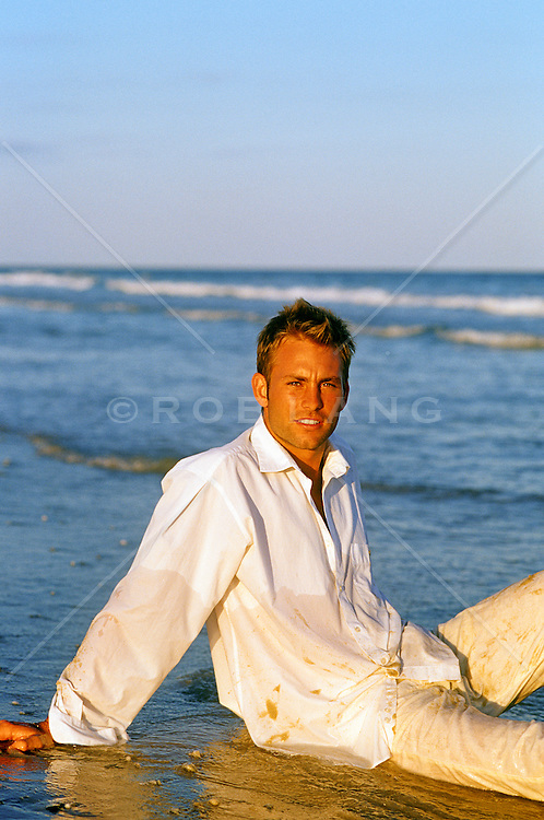 good looking man sitting in the water at the beach during sunset