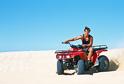 Man riding his ATV on a sand dune