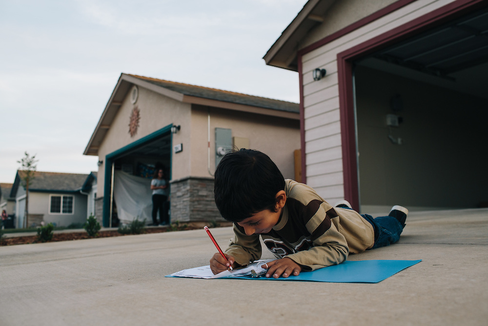 Gerardo Ramirez Hernandez, 6, does his math homework in the driveway of his home in Madera, California. The Hernandez family received solar panels from Grid Alternatives.